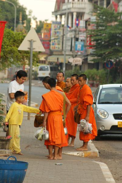 Father and son giving alms to Buddhist Monks