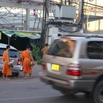 Rushing across the street to give alms to Buddhist monks